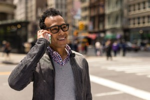 Young African Asian man in New York City talking on his cell phone