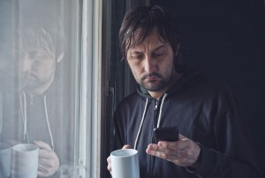 An unkempt, unshaven man in a sweatshirt drinking coffee and sending a text message on his smart phone
