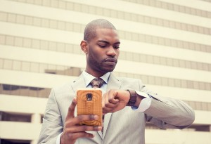 Businessman texting on smart phone and looking at his watch