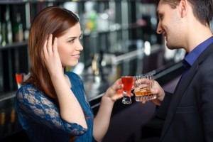 A woman moves hair out of her face while speaking with a man over drinks at a bar