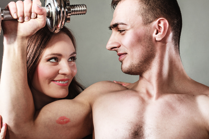 a man flexes his bicep while he and a woman gaze at each other
