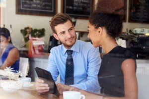 young man in a shirt and tie listens to a woman speak to him in a coffee shop
