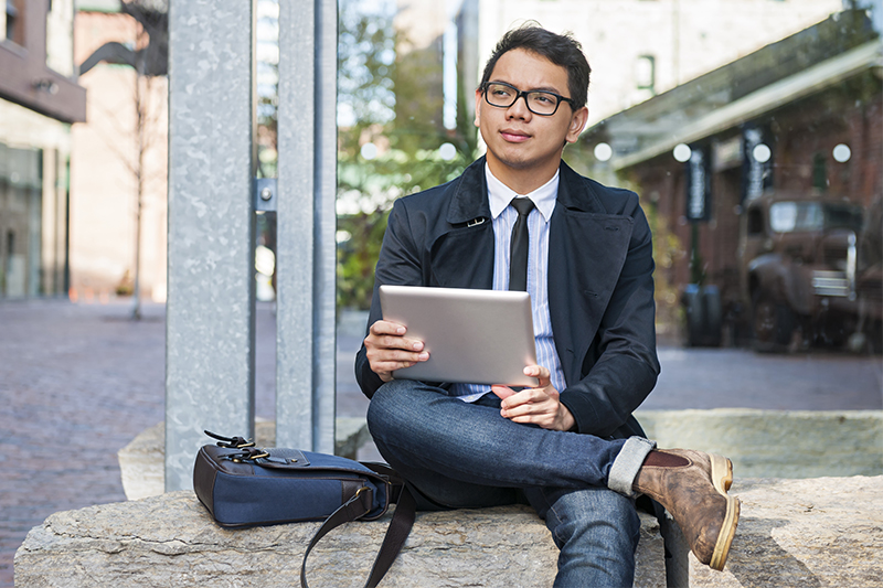 An Asian man sits on a bench holding a tablet